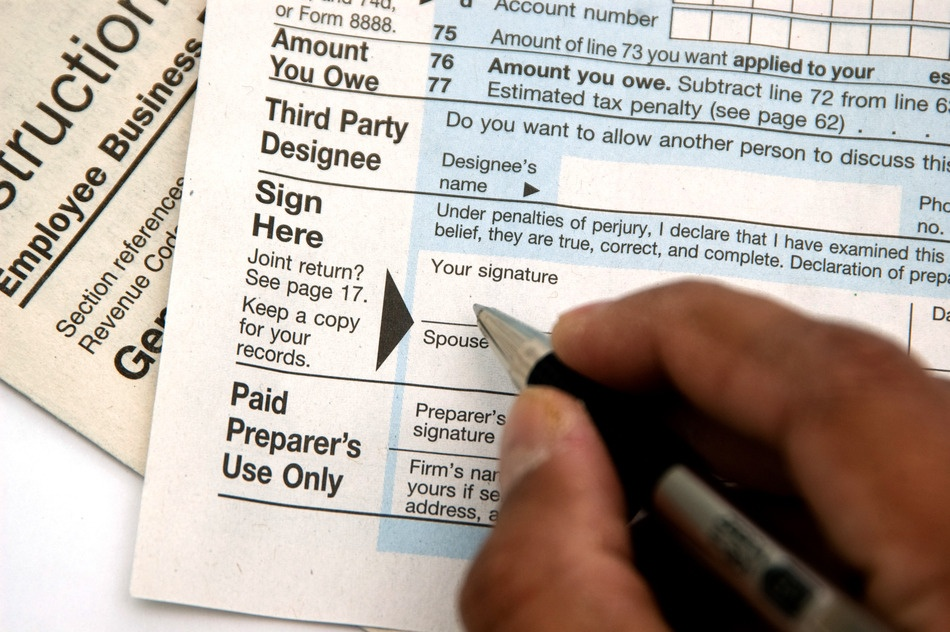 photodune-2545685-hand-signing-a-tax-form-concept-of-filing-tax-s